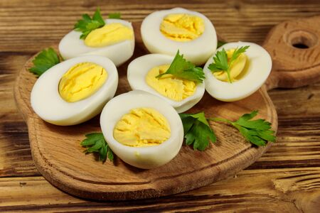 Boiled eggs with parsley on cutting board on a wooden table