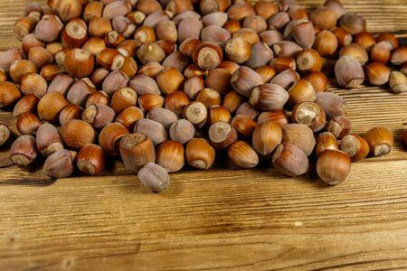 Heap of hazelnuts on a wooden table 写真素材 - 131922986