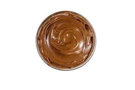 Glass bowl with delicious chocolate hazelnut spread isolated on white background. Top view