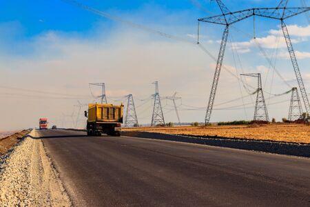 Trucks driving on asphalt road along fields and power line