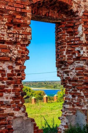 View through window hole of ruined red brick building