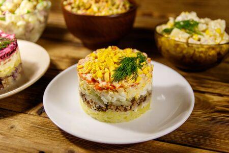 Set of festive mayonnaise salads on wooden table Zdjęcie Seryjne - 131786515