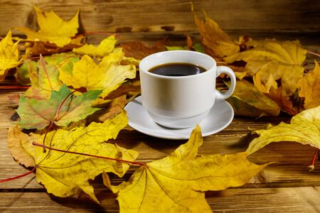 Cup of coffee and autumn maple leaves on wooden table. Autumn concept