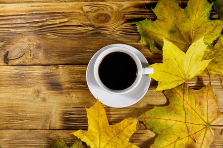 Cup of coffee and autumn maple leaves on wooden table. Top view. Autumn concept
