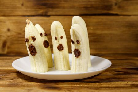 Homemade Halloween scary banana ghosts monsters with chocolate faces. Funny dessert for Halloween party on wooden table Reklamní fotografie