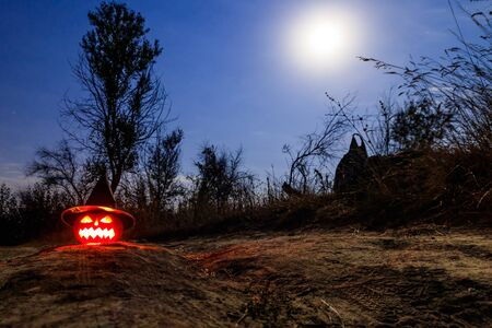 Spooky Halloween pumpkin jack-o-lantern in witch hat with burning candles in scary forest at night
