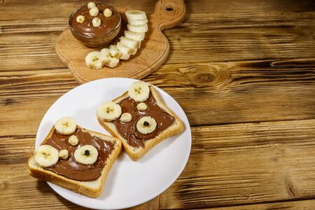 Two sweet sandwiches with delicious chocolate hazelnut spread and banana in shape of bear on wooden table