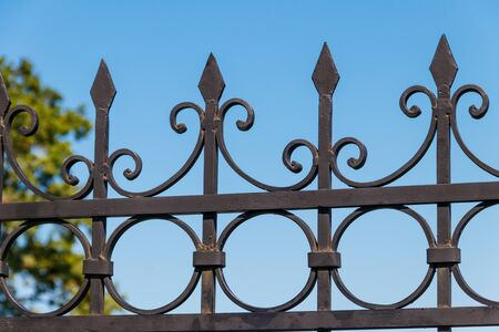 Black wrought iron fence in city park
