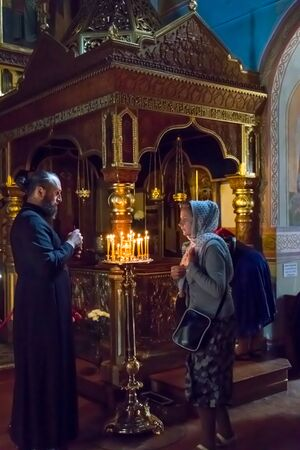 Murom, Russia - August 12, 2019: Orthodox priest and believers in Trinity cathedral of Holy Trinity convent in Murom, Russia