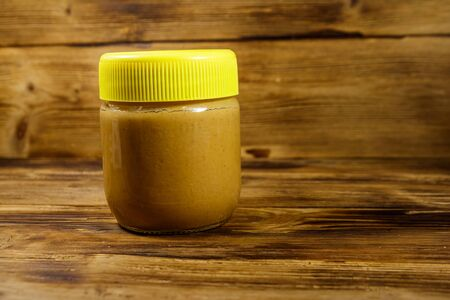 Jar of peanut butter on a wooden table Imagens