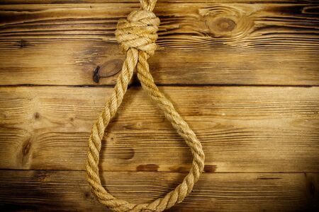 Deadly loop of rope on a wooden background. Concept of death penalty or suicide Imagens