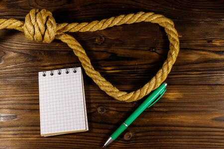 Deadly loop of rope and suicide note on a wooden background. Concept of suicide
