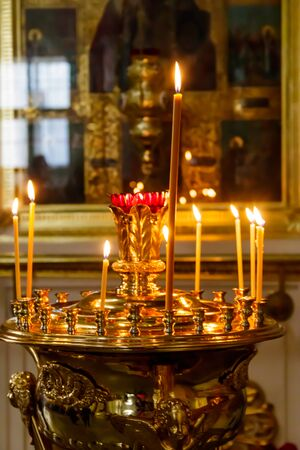 Large church golden candlestick with burning candles in orthodox church