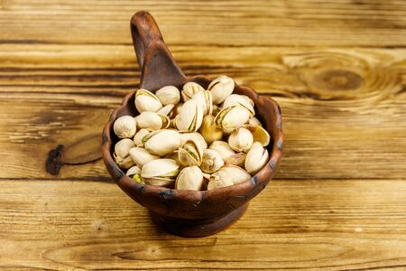 Pistachio nuts in ceramic bowl on a wooden table