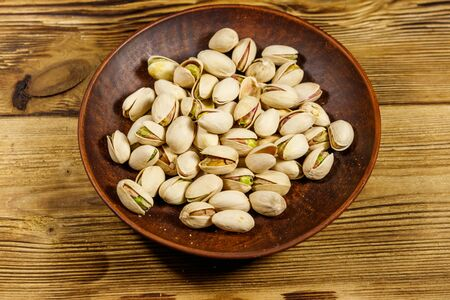Pistachio nuts in ceramic plate on a wooden table