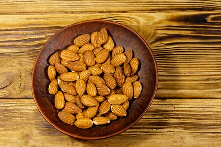 Almonds in ceramic plate on a rustic wooden table. Top view Stock Photo - 133311808