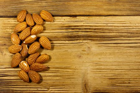 Almonds on a rustic wooden table. Top view, copy space