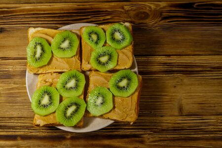 Tasty sandwiches with peanut butter and kiwi fruits on wooden table. Top view