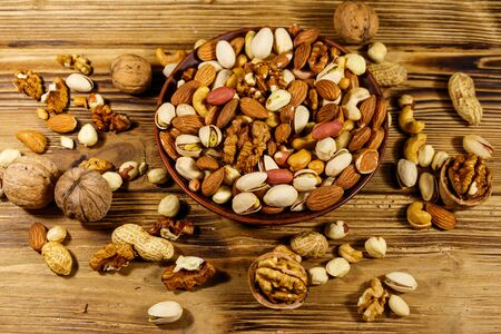Mixed nuts on wooden table. Walnuts, pistachio, almond, peanut, cashew, hazelnut in ceramic bowl. Healthy eating concept Imagens