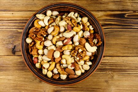 Mixed nuts on wooden table. Walnuts, pistachio, almond, peanut, cashew, hazelnut in ceramic bowl. Healthy eating concept. Top view Imagens