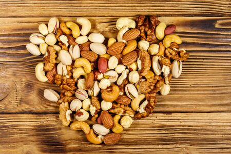 Pile of mixed nuts in shape of heart on wooden table. Top view. Walnuts, pistachio, almond, peanut, cashew, hazelnut on wood background. Healthy eating concept Imagens