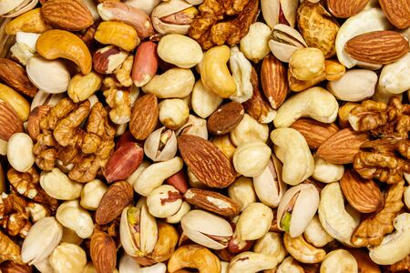 Background of mixed nuts (walnuts, pistachio, almond, peanut, cashew, hazelnut). Healthy eating concept Imagens