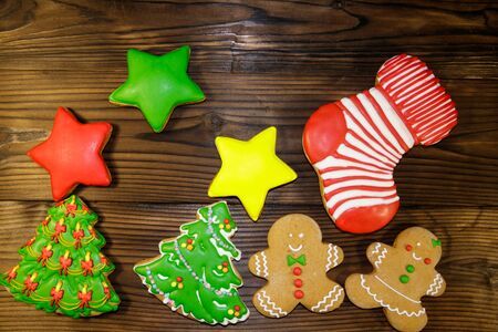 Tasty festive Christmas gingerbread cookies in the shape of Christmas tree, Gingerbread man, star and Christmas stocking on wooden table. Top view