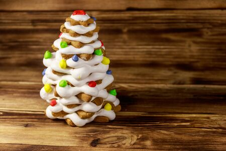 Gingerbread Christmas tree decorated with glaze on wooden table Imagens