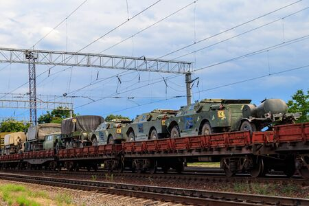Cargo train carrying military vehicles on railway flat wagons