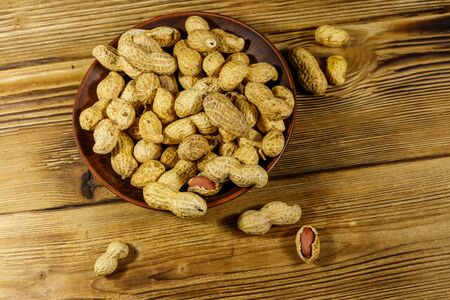 Peanuts in nutshell on a wooden table. Top view Stock Photo