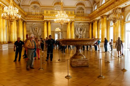 St. Petersburg, Russia - June 26, 2019: Visitors in Armorial Hall of Winter palace (State Hermitage Museum) in St. Petersburg, Russia