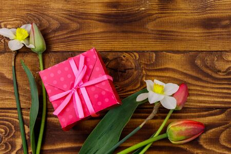 Gift box and bouquet of red tulips and daffodils on wooden background. Concept of Valentines Day, Womens Day, Mothers Day and Birthday. Top view, copy space