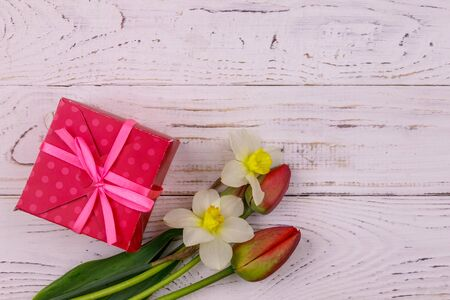 Gift box and bouquet of red tulips and daffodils on white wooden background. Concept of Valentines Day, Womens Day, Mothers Day and Birthday. Top view, copy space