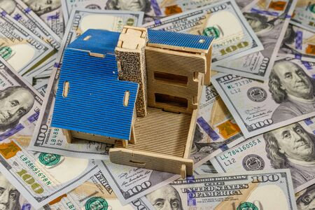 House model on background of U.S. one hundred dollar bills. Property investment, home loan, house mortgage, real estate concept