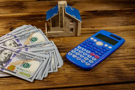 House model, U.S. one hundred dollar bills and calculator on wooden background. Property investment, home loan, house mortgage, real estate concept Banco de Imagens