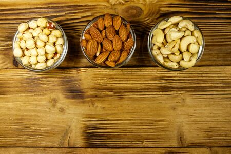 Assortment of nuts on wooden table. Almond, hazelnut and cashew in glass bowls. Top view, copy space. Healthy eating concept
