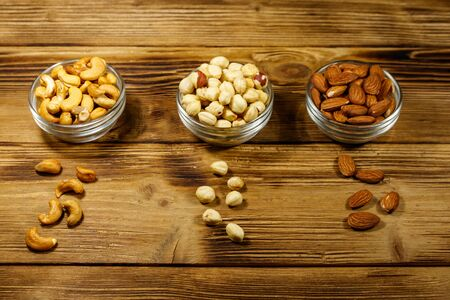 Assortment of nuts on wooden table. Almond, hazelnut and cashew in glass bowls. Healthy eating concept