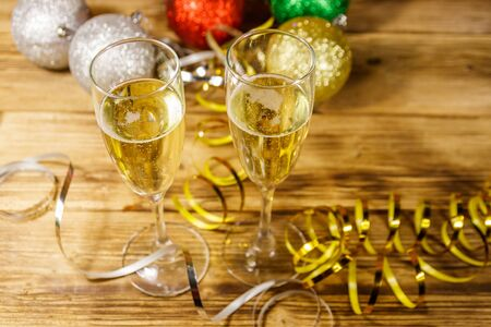 Two glasses of champagne and festive Christmas decorations on wooden table. Christmas and New Year celebration 写真素材 - 134842294