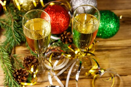 Two glasses of champagne and festive Christmas decorations on wooden table. Christmas and New Year celebration 写真素材 - 134842295