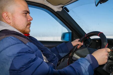 Young man driving a car on winter road. Inside view