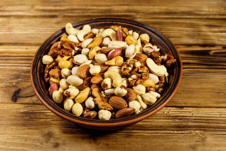 Mixed nuts on wooden table. Walnuts, pistachio, almond, peanut, cashew, hazelnut in ceramic bowl. Healthy eating concept 写真素材