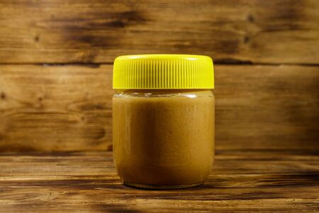 Jar of peanut butter on a wooden table 写真素材 - 134842571