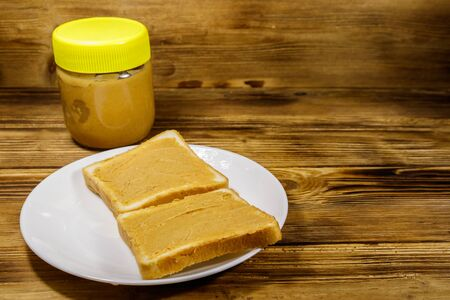 Jar of peanut butter and plate with two sandwiches with peanut butter on wooden table