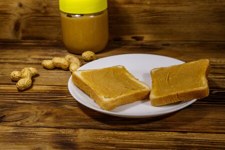 Jar of peanut butter and plate with two sandwiches with peanut butter on wooden table 写真素材 - 134842578