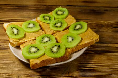 Tasty sandwiches with peanut butter and kiwi fruits on wooden table