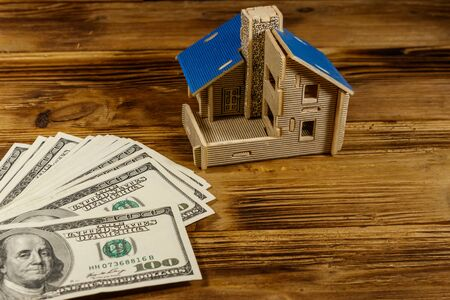 House model and U.S. one hundred dollar bills on wooden background. Property investment, home loan, house mortgage, real estate concept 写真素材