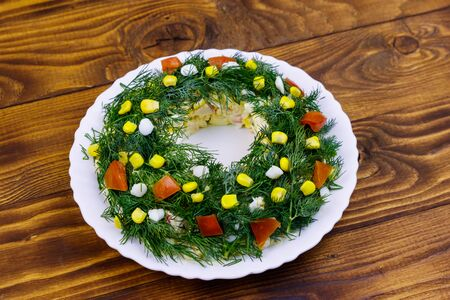 Salad Christmas wreath on a wooden table