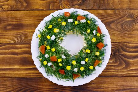 Salad Christmas wreath on a wooden table. Top view