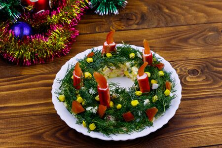 Salad Christmas wreath and Christmas decorations on a wooden table