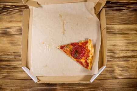 Last slice of pizza in cardboard box on a wooden table. Top view. Concept for home delivery of food, fast food, delivery of pizza 写真素材 - 134956916